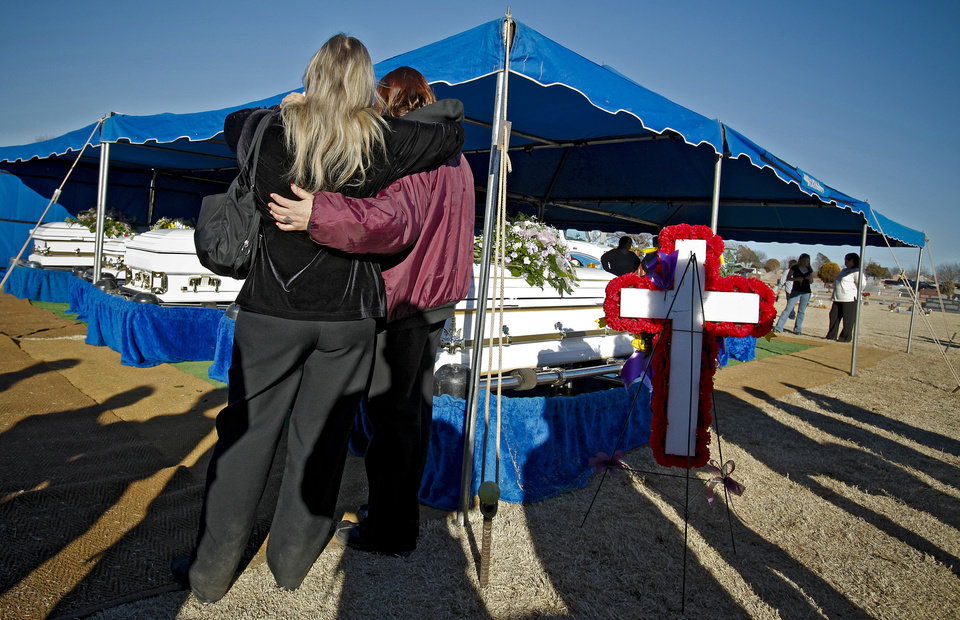 Photo - Mourners gather around the five caskets of Summer Rust and her four children Kirsten Rust, Autumn Rust, Teagin Rust and Evynn Garas after graveside services at the El Reno Cemetery in El Reno, Okla. on Wednesday, Jan. 21, 2009. Rust and her children were killed earlier this month in their apartment in El Reno, Okla. 