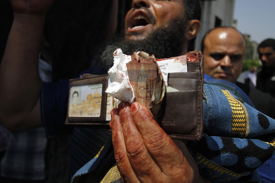 Photo - A man displays a bloodied wallet belonging to a supporter of ousted President Mohamed Morsi's outside a local hospital in Cairo. Egypt, Monday, July 8, 2013. Egyptian soldiers and police opened fire on supporters of the ousted president early Monday in violence that left dozens of people killed, including one officer, outside a military building in Cairo where demonstrators had been holding a sit-in, government officials and witnesses said.  .(AP Photo/Nasser Shiyoukhi)