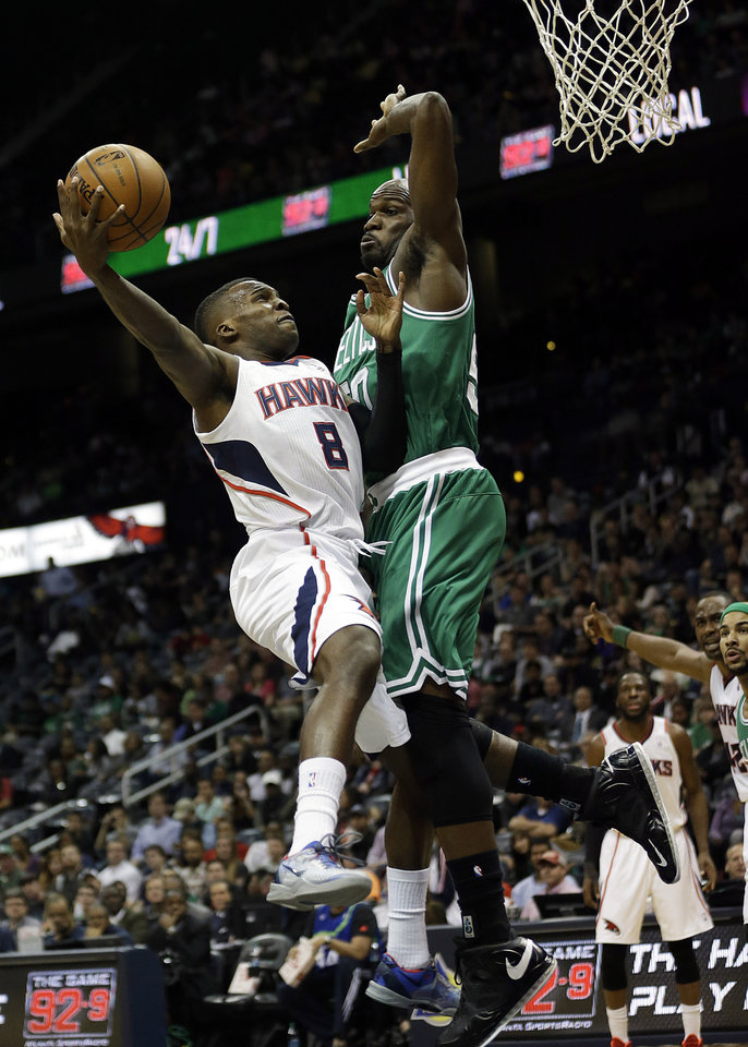 Photo - Atlanta Hawks' Shelvin Mack, left, puts up a shot against the defense of Boston Celtics' Joel Anthony in the second quarter of an NBA basketball game, Wednesday, April 9, 2014, in Atlanta. (AP Photo/David Goldman)