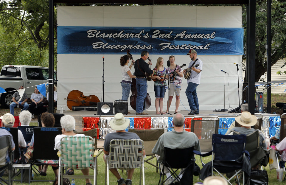 Audience members sit back and enjoy the music as Heartbreak Line performs Saturday at the Blanchard Bluegrass Festival.