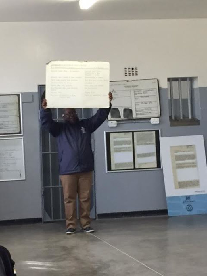 Photo - A political prisoner who spent nearly seven years on Robben Island holds up a placard detailing what inmates got for food. Hint: It ain't much.