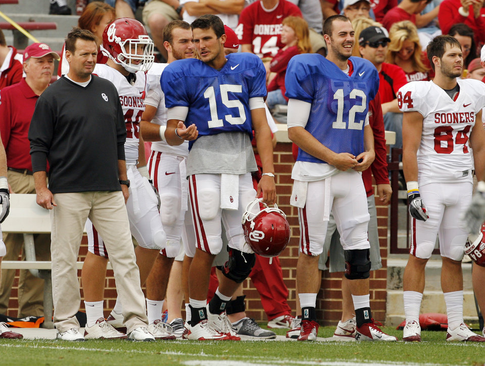 Photo - Head coach Bob Stoops and quarterbacks Drew Allen (15) and Landry Jones (12) stand on the sidelines during the University of Oklahoma (OU) football team's annual Red and White Game at Gaylord Family/Oklahoma Memorial Stadium on Saturday, April 14, 2012, in Norman, Okla.  Photo by Steve Sisney, The Oklahoman