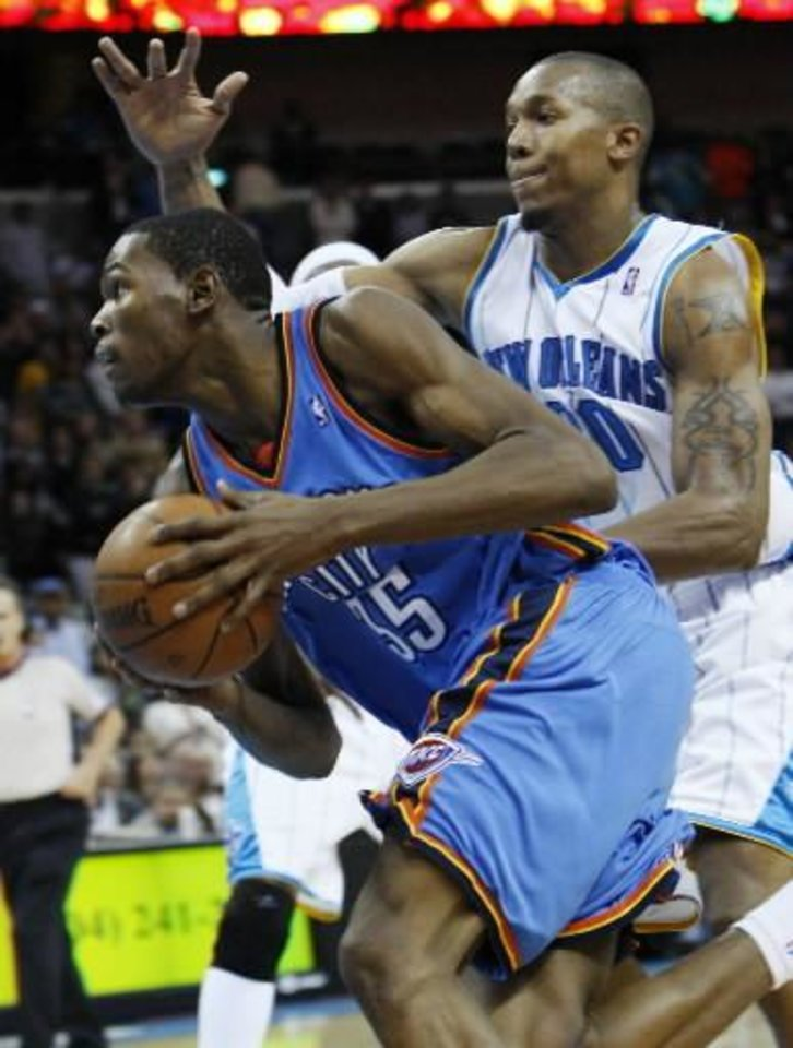 Photo - Oklahoma City  Thunder guard Kevin Durant, left, drives to the basket against New Orleans Hornets forward David West, right, during the fourth quarter of an NBA basketball game in New Orleans, Saturday, Nov. 22, 2008. Despite Durant's team-high 30 points, the Hornets beat the  Thunder 109-97. (AP Photo/Ann Heisenfelt)