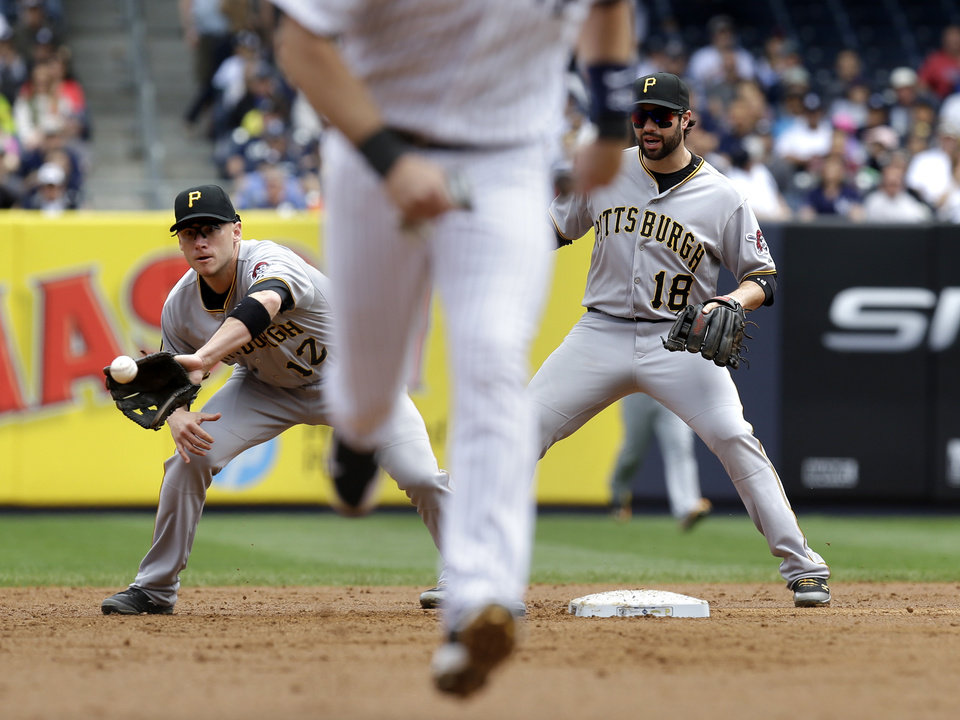 Photo - Pittsburgh Pirates' Clint Barmes, left, makes the catch and turns a double play while teammate second baseman Neil Walker looks on during the first inning of the first baseball game of a double-header against the New York Yankees at Yankee Stadium, Sunday, May 18, 2014 in New York. (AP Photo/Seth Wenig)