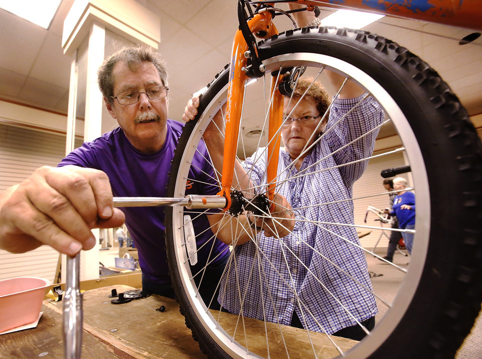 Bill and Tina Elliott, Oklahoma City, work as a team to assemble a bicycle. This is the couple\'s second year to volunteer with the project. More than 150 volunteers donated their time and skills Saturday morning, Dec. 1, 2012, assembling 830 childrens\' bicycles for the Salvation Army\'s bike giveaway project. The bicycles will be distributed to children in need at Christmas. Bikes were assembled inside the former J.C. Penney store in the vacant Crossroads Mall. Photo by Jim Beckel, The Oklahoman
