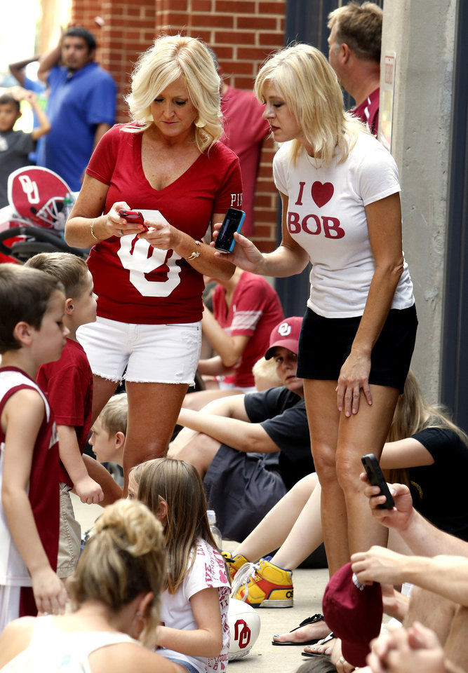 Photo - Fans Mollie Hager, left, and Lee Ann Hooker show their love for the team and coach as they wait to enter the stadium for fan appreciation day for the University of Oklahoma Sooner (OU) football team at Gaylord Family-Oklahoma Memorial Stadium in Norman, Okla., on Saturday, Aug. 3, 2013. Photo by Steve Sisney, The Oklahoman
