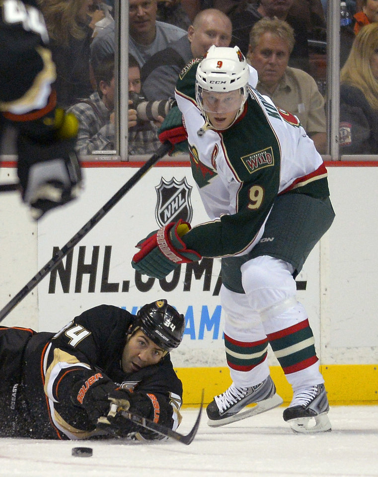 Anaheim Ducks center Daniel Winnik, below, reaches for the puck as Minnesota Wild center Mikko Koivu, of Finland, looks on during the first period of an NHL hockey game, Friday, Feb. 1, 2013, in Anaheim, Calif. (AP Photo/Mark J. Terrill)