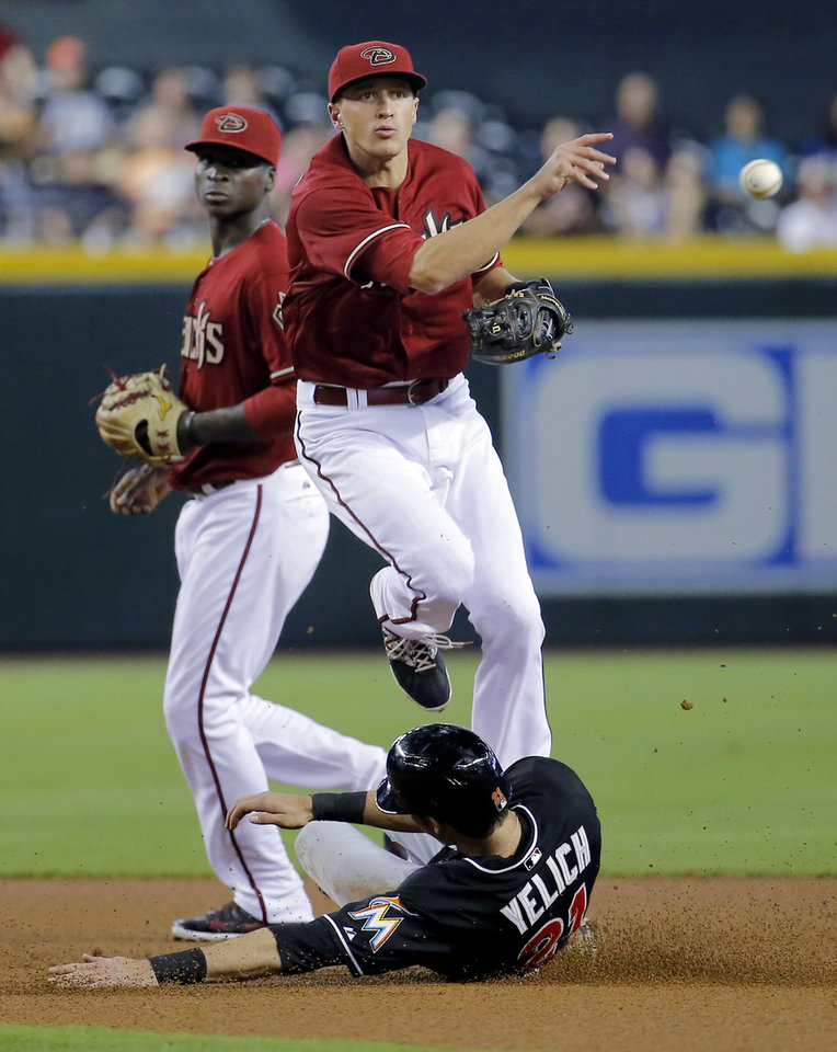 Photo - Miami Marlins' Christian Yelich is forced out by Arizona Diamondbacks' Nick Ahmed as he turns a double play on Marlins' Donovan Solano during the first inning of a baseball game, Wednesday, July 9, 2014, in Phoenix. (AP Photo/Matt York)
