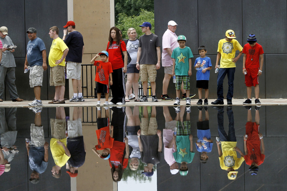 Photo - Visitors at the Oklahoma City National Memorial &  Museum, are mirrored in the water of the Reflecting Pool as they stand in front of the west Gate of Time on Saturday afternoon, June 16,  2012.    Photo by Jim Beckel, The Oklahoman