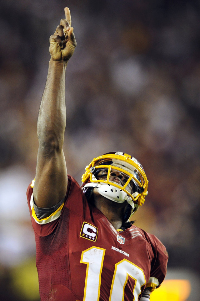 Photo - Washington Redskins quarterback Robert Griffin III points skyward after throwing a touchdown pass to wide receiver Pierre Garcon during the second half of an NFL football game against the New York Giants in Landover, Md., Monday, Dec. 3, 2012. (AP Photo/Nick Wass)