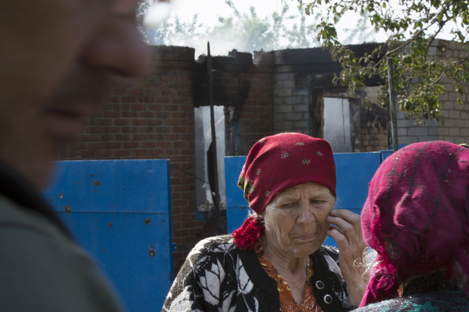 Photo - Local citizens talk to each other in front of a house destroyed by shellings in Semyonovka village, outside Slovyansk, Ukraine, Friday, May 23, 2014. The village on the outskirts of Slovyansk, a city which has been the epicenter of clashes for weeks, has seen continuous shelling by the Ukrainian government forces, who have retaliated to the rebel fire. On Friday, a private house was destroyed by mortar fire that came from the Ukrainian side. There were no casualties, as the family living there had left the previous day, according to local residents. (AP Photo/Alexander Zemlianichenko)