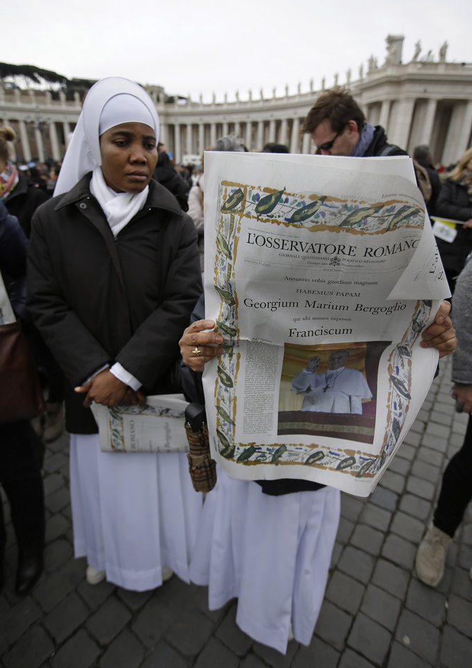 Nuns read a copy of the L'Osservatore Romano, the official Vatican newspaper, in St. Peter's Square, ahead of the Angelus prayer with Pope Francis Sunday, March 17, 2013. (AP Photo/Gregorio Borgia)