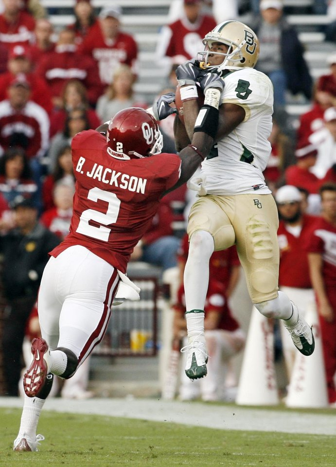 Photo - David Gettis (4) catches a long pass over defender Brian Jackson (2) during the second half of the college football game between The University of Oklahoma Sooners (OU) and the Baylor Bears at the Gaylord Family-Oklahoma Memeorial Stadium on Saturday, Oct. 10, 2009, in Norman, Okla.