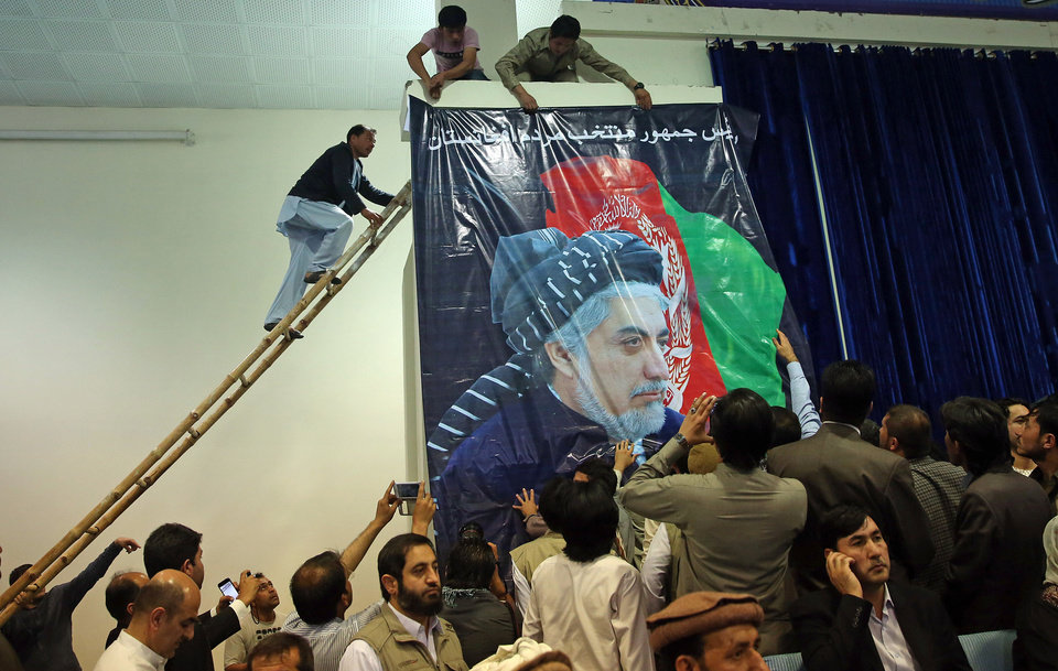 Photo - Supporters of Afghan presidential candidate Abdullah Abdullah, install his picture instead of president Hamid Karzai's picture, during a gathering of his supporters in Kabul, Afghanistan, Tuesday, July 8, 2014.  Abdullah says he received calls from President Barack Obama and U.S. Secretary of State John Kerry after he refused to accept the preliminary result of the vote citing fraud. He told his supporters the results of the election were fraudulent but asked them to give him a few more days to negotiate. (AP Photo/Massoud Hossaini)