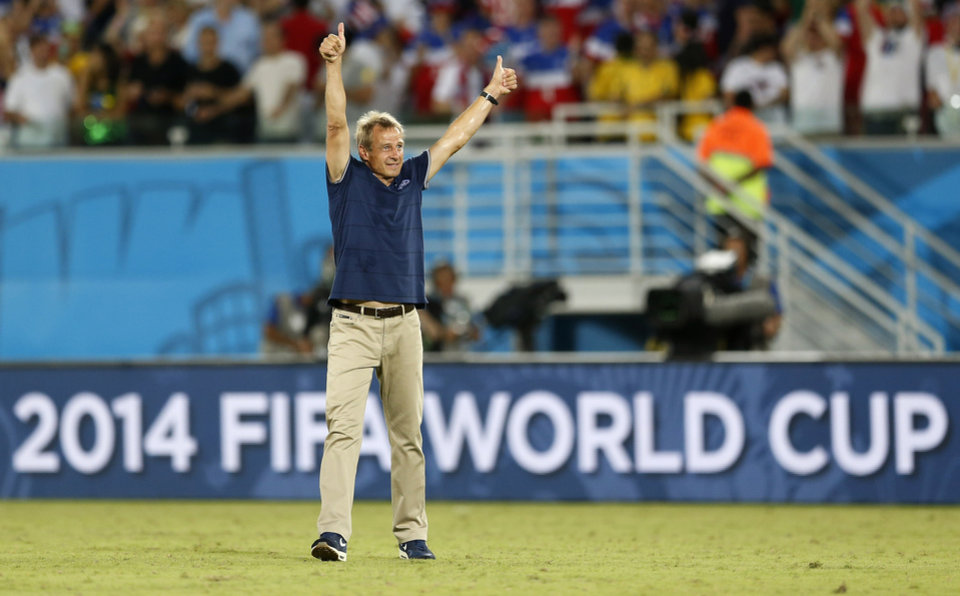 Photo - United States' head coach Juergen Klinsmann celebrates after his team's 2-1 victory over Ghana during the group G World Cup soccer match between Ghana and the United States at the Arena das Dunas in Natal, Brazil, Monday, June 16, 2014. (AP Photo/Julio Cortez)