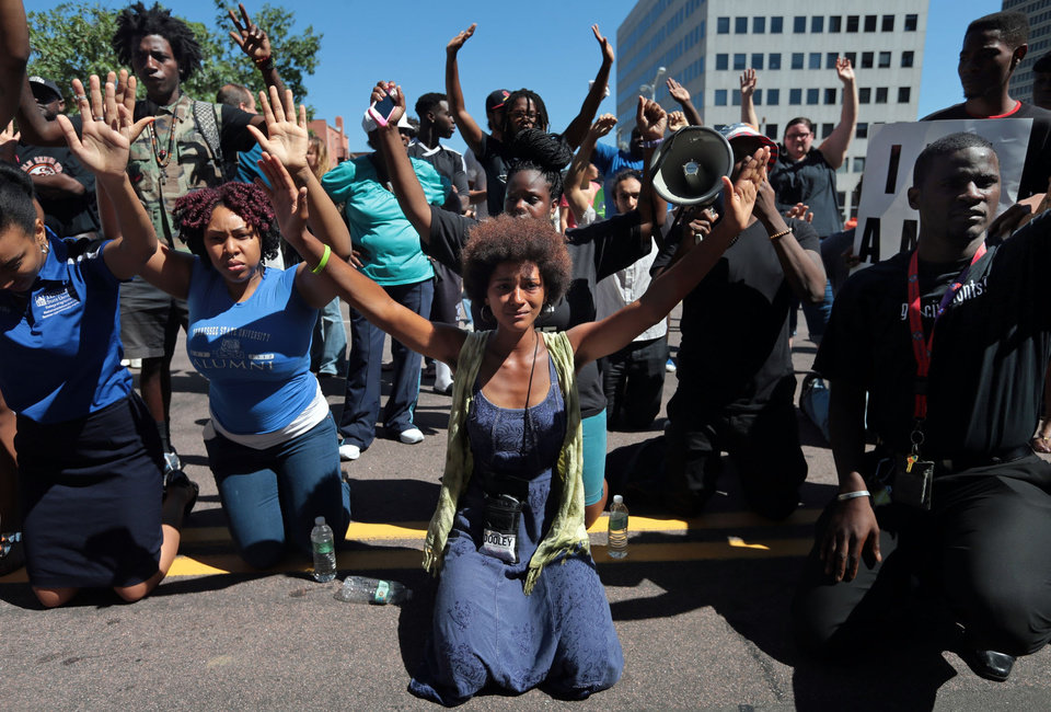 Photo - Protestors drop to their knees and put their arms in the air during a rally for Michael Brown Jr., who was shot and killed by a Ferguson police officer last Saturday, Tuesday, Aug. 12, 2014, in Clayton, Mo. (AP Photo/St. Louis Post-Dispatch, Laurie Skrivan)