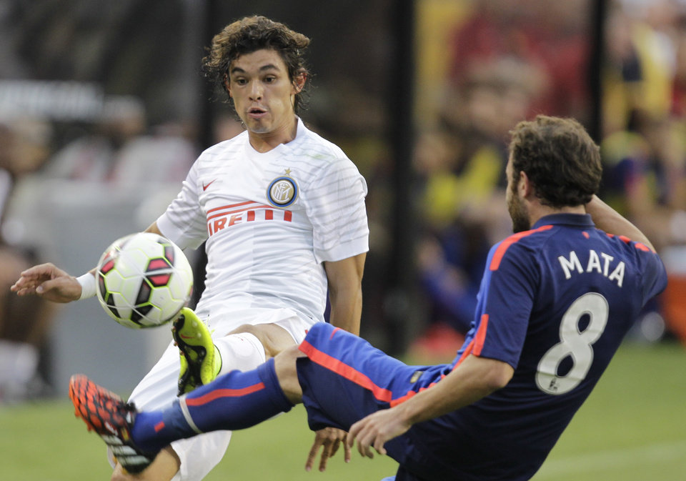 Photo - Inter Milan's Dodo, left, and Manchester United's Juan Mata (8) kick the ball during the first half of a soccer game at  the 2014 Guinness International Champions Cup, Tuesday, July 29, 2014, in Landover, Md. Manchester United won 5-3 in a penalty kick shootout. (AP Photo/Luis M. Alvarez)