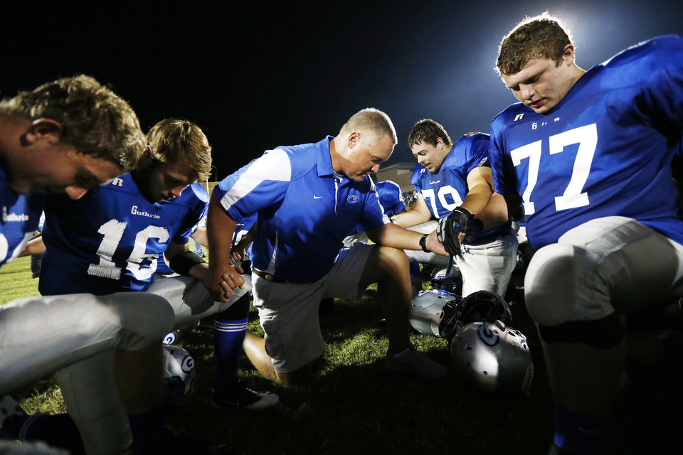 Guthrie head coach Rafe Watkins prays with his players after a high school football game between Guthrie and Guymon at Jelsma Stadium in Guthrie, Okla., Friday, Sept. 21, 2012. Watkins has watched the last 8 games from the stands as he served a suspension dating back to last year. Photo by Nate Billings, The Oklahoman
