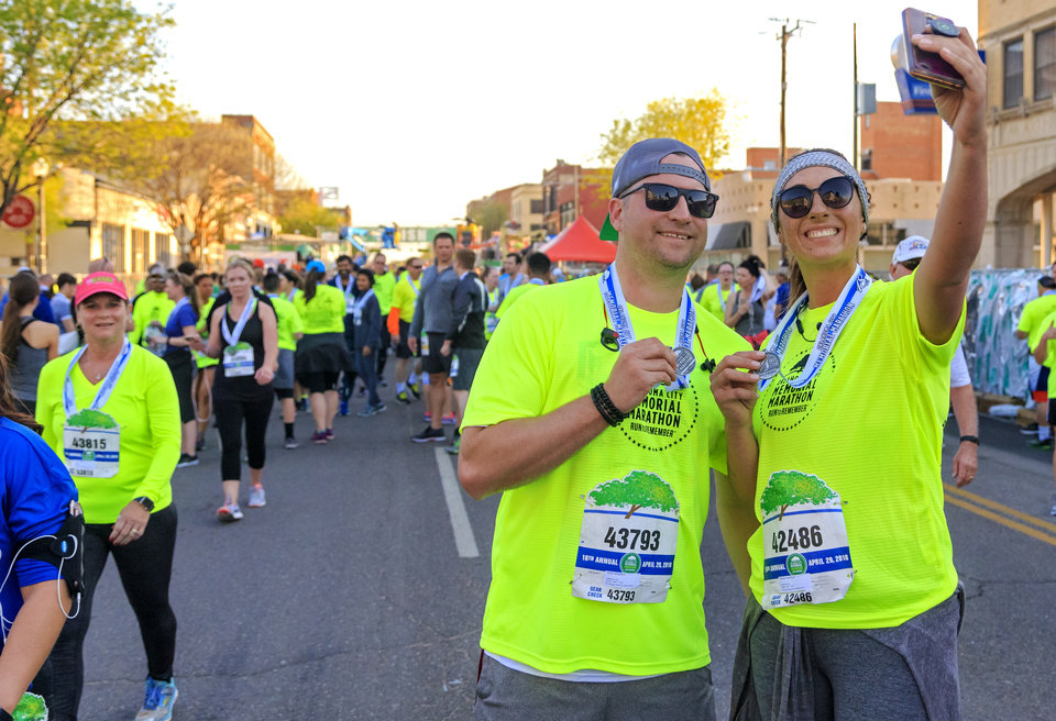 Photo - Ricky Kirkpatrick and Morgan Northcutt take a selfie after finishing the 5K race during the Oklahoma City Marathon in Oklahoma City, Okla. on Sunday, April 29, 2018.  . Photo by Chris Landsberger, The Oklahoman
