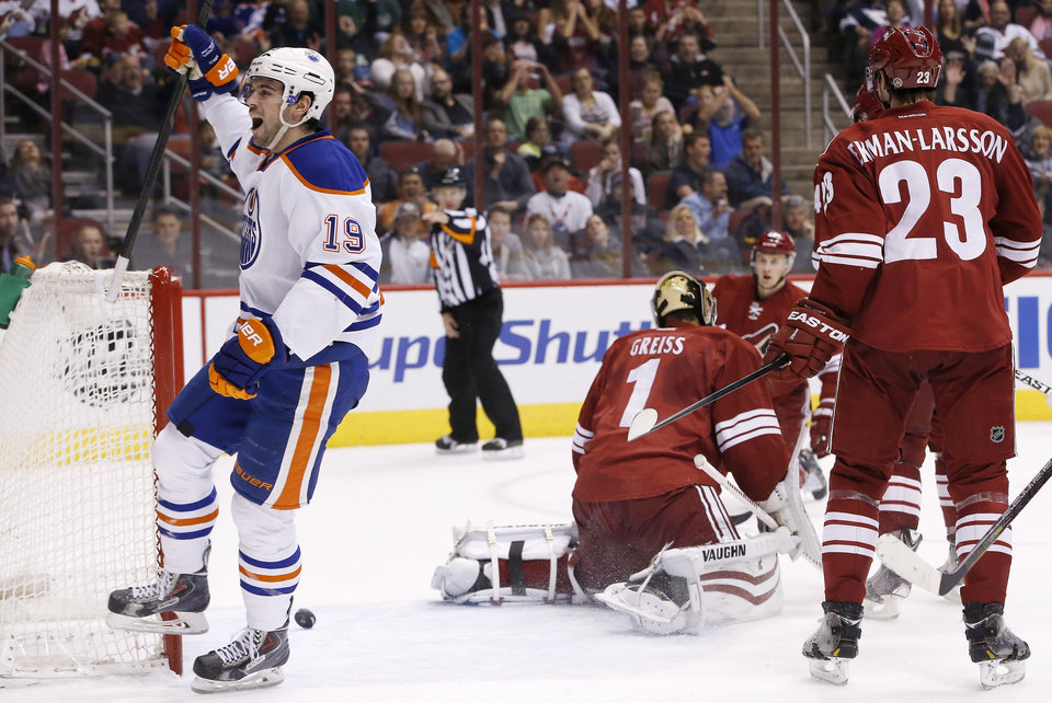 Photo - Edmonton Oilers' Justin Schultz (19) celebrates his goal against Phoenix Coyotes' Thomas Greiss (1), of Germany, as Coyotes' Oliver Ekman-Larsson (23), of Sweden, and Lauri Korpikoski, rear, of Finland, watch during the first period of an NHL hockey game, Friday, April 4, 2014, in Glendale, Ariz. (AP Photo/Ross D. Franklin)