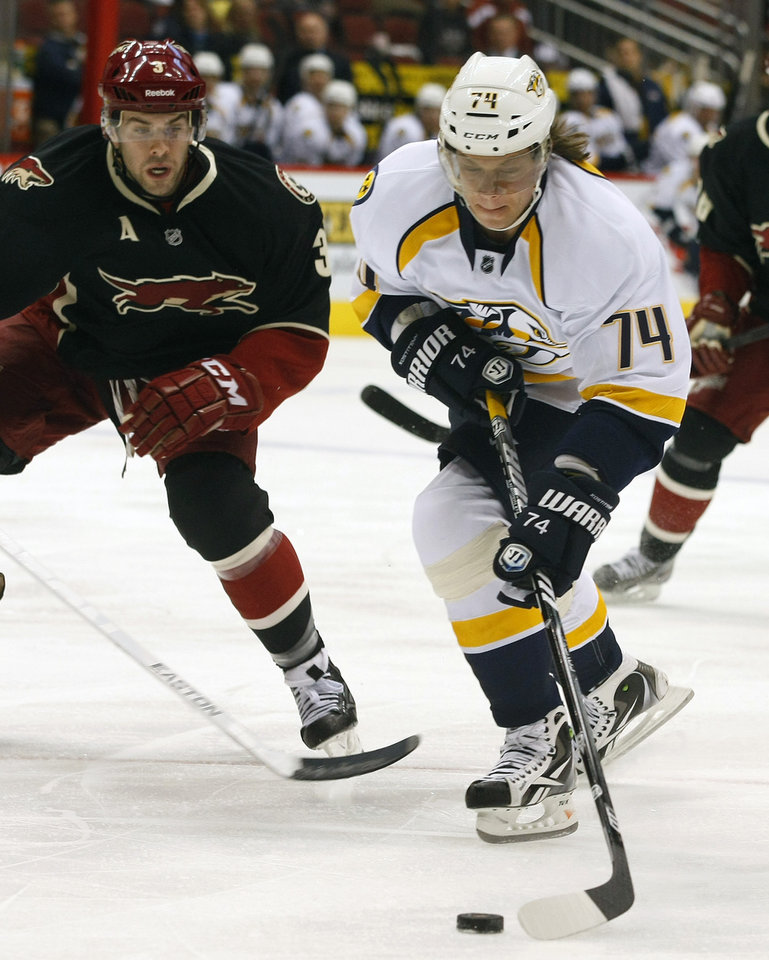 Nashville Predators left wing Sergei Kostitsyn (74) of Belarus, shoots on goal in front of Phoenix Coyotes defenseman Keith Yandle (3) during an NHL hockey game on Monday, Jan. 28, 2013, in Glendale, Ariz. (AP Photo/Rick Scuteri)