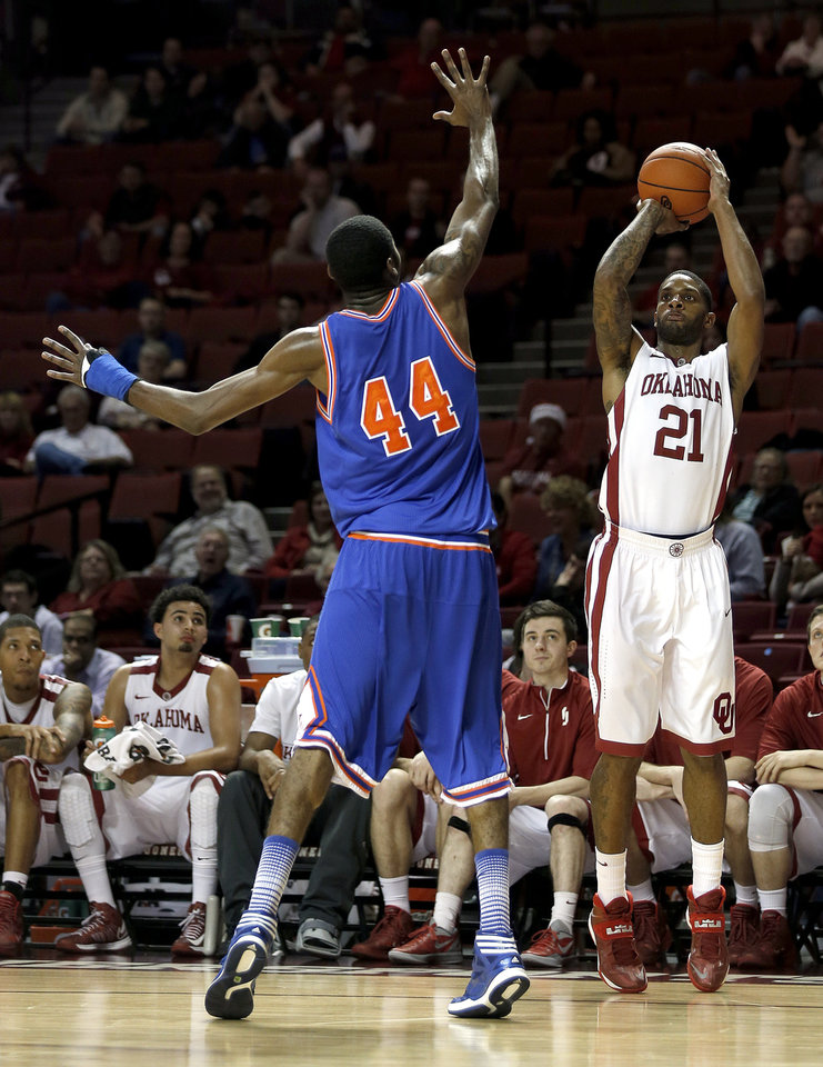 Oklahoma's Cameron Clark (21) shoots as Texas-Arlington's Anthony Walker (44) during the men's college basketball game between the University of Oklahoma and UT-Arlington, at the LLoyd Noble Center in Norman, Okla. Tuesday, Dec. 17, 2013. Photo by Sarah Phipps, The Oklahoman