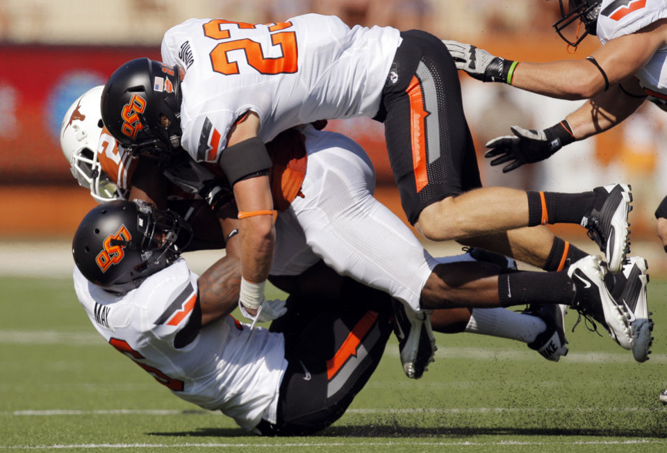 Photo - Oklahoma State's Zack Craig (23) and Andrae May (16) tackle Texas' Fozzy Whittaker (2) in the first half during a college football game between the Oklahoma State University Cowboys (OSU) and the University of Texas Longhorns (UT) at Darrell K Royal-Texas Memorial Stadium in Austin, Texas, Saturday, Oct. 15, 2011. Photo by Nate Billings, The Oklahoman