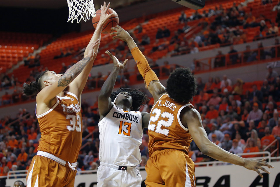 Photo - Oklahoma State's Isaac Likekele (13) has his shot blocked as he attempts a shot between Texas' Kamaka Hepa (33) and Kai Jones (22) during an NCAA basketball game between the Oklahoma State University Cowboys (OSU) and the Texas Longhorns at Gallagher-Iba Arena in Stillwater, Okla., Wednesday, Jan. 15, 2020. Oklahoma State lost 76-64. [Bryan Terry/The Oklahoman]