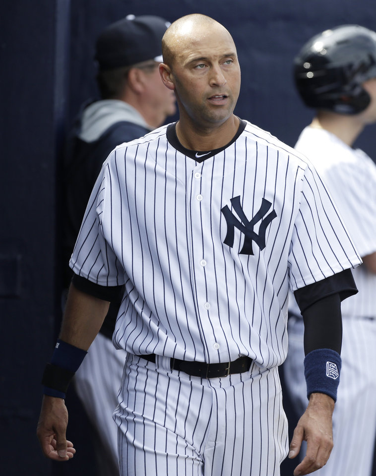 Photo - New York Yankees shortstop Derek Jeter walks in the dugout during the fourth inning of an exhibition baseball game against the Pittsburgh Pirates Thursday, Feb. 27, 2014, in Tampa, Fla. (AP Photo/Charlie Neibergall)