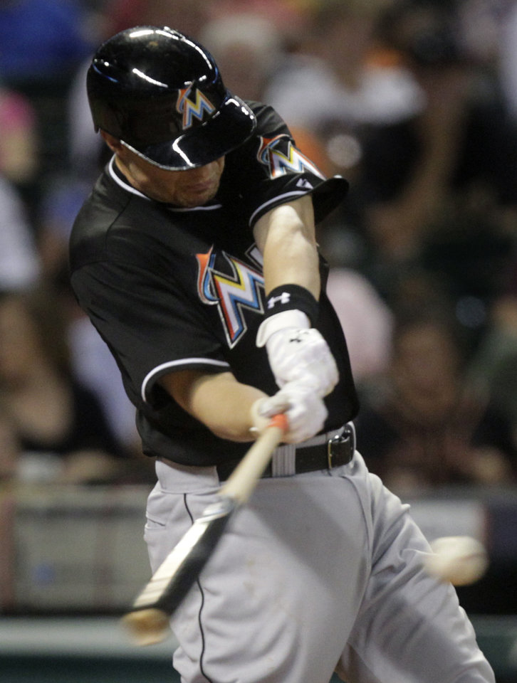 Photo - Miami Marlins' Jeff Baker singles to left field during the eighth inning of a baseball game against the Houston Astros, Friday, July 25, 2014, in Houston. (AP Photo/Patric Schneider)
