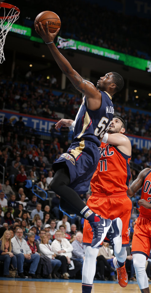 Photo - New Orleans' E'Twaun Moore (55) drives to the basket in front of Oklahoma City's Enes Kanter (11) during the NBA game between the Oklahoma City Thunder and the New Orleans Pelicans at the Chesapeake Energy Arena,  Sunday, Dec. 4, 2016. Photo by Sarah Phipps, The Oklahoman