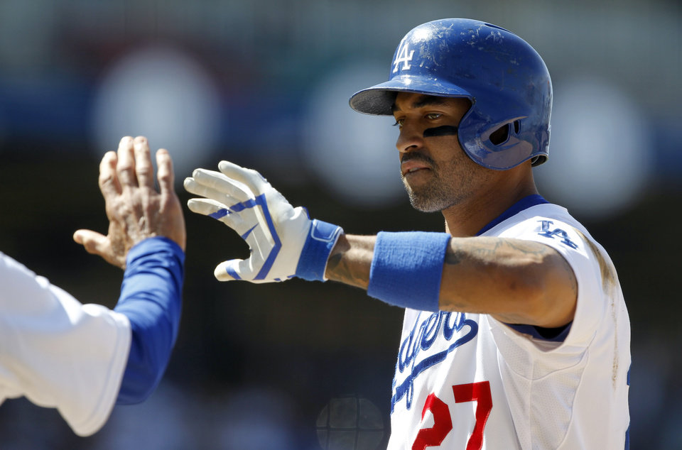 Photo - Los Angeles Dodgers' Matt Kemp gets a high-five from first base coach Davey Lopes after hitting an RBI-single to score Yasiel Puig in the sixth inning of a baseball game against the San Francisco Giants, Saturday, May 10, 2014, in Los Angeles. (AP Photo/Alex Gallardo)