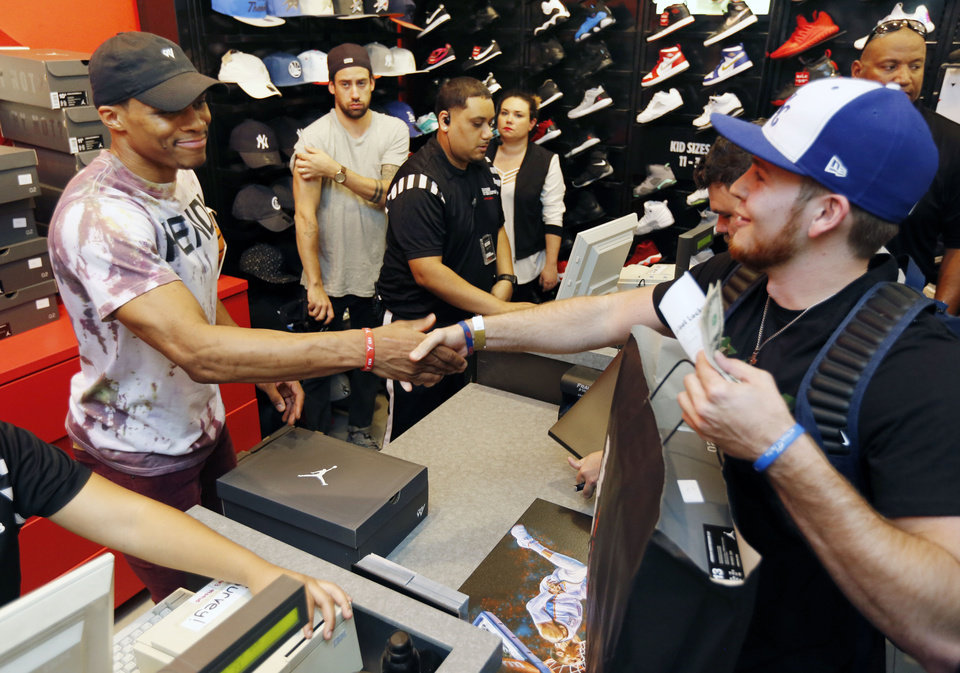 Photo - Russell Westbrook shakes hands with fan Ty Richey at the Foot Locker inside Penn Square Mall in Oklahoma City, Okla. as he debuts his new Jordan Brand shoe, Saturday, Oct. 15, 2016.  Photo by Paul Hellstern, The Oklahoman