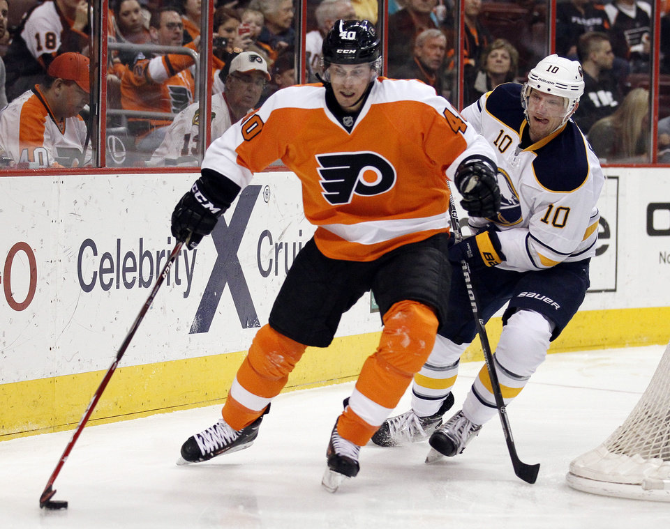Photo - Philadelphia Flyers' Vincent Lecavalier, left, controls the puck while trailed by Buffalo Sabres' Christian Ehrhoff behind the Sabres' net, during the second period of an NHL hockey game, Sunday, April 6, 2014, in Philadelphia. The Flyers won 5-2.  (AP Photo/Tom Mihalek)