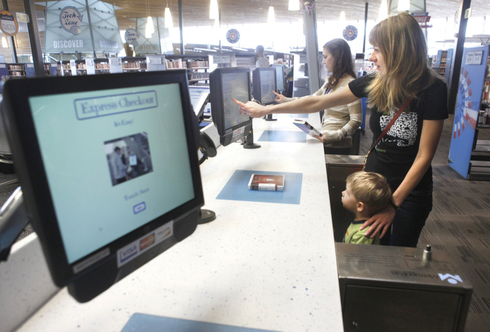 Photo - Lyuda Polyun and her son, Andrew Bessonov, 3, use the self-pickup system at Northwest Library.  Photo by Paul Hellstern, The Oklahoman