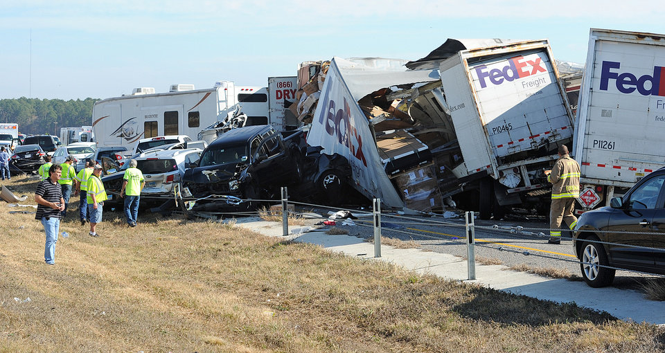 Photo -   Cars and Trucks are piled on Interstate 10 in Southeast Texas Thursday Nov. 22, 2012. The Texas Department of Public Safety says at least 35 people have been injured in a more than 50-vehicle pileup. (AP Photo/The Beaumont Enterprise, Guiseppe Barranco)
