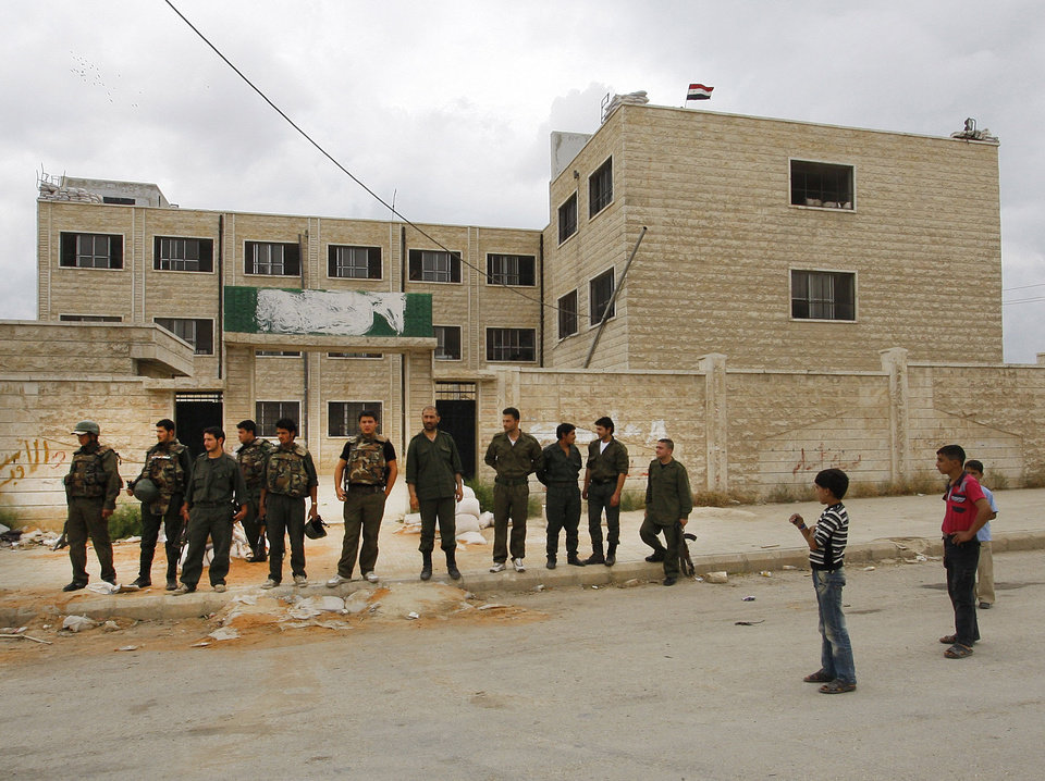 Photo -   In this picture taken during a UN observer-organized tour, Syrian boys, right, look at Syrian army soldiers, left, as they stand outside a school building used as a temporary military base in Hama city, central Syria, on Thursday, May 3, 2012. Syrian security forces stormed dorms at a northwestern university to break up anti-government protests there, killing at least four students and wounding several others with tear gas and live ammunition, activists and opposition groups said Thursday. (AP Photo/Muzaffar Salman)