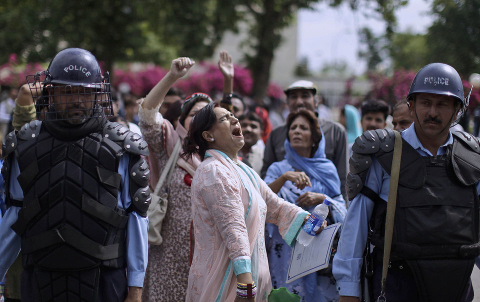 Photo -   Pakistani riot policemen stand guard, as a supporter of Prime Minister Yousuf Raza Gilani, center, shouts slogans in Gilani's support, outside the Supreme court in Islamabad, Pakistan, Thursday, April 26, 2012. The Supreme Court convicted Gilani of contempt on Thursday for refusing to reopen an old corruption case against President Asif Ali Zardari , but spared him a prison term in a case that has stoked political tensions in the country. (AP Photo/Muhammed Muheisen)