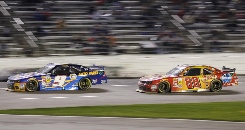 Photo - Chase Elliott (9) leads Dale Earnhardt Jr. (88) during the NASCAR Nationwide Series auto race at Texas Motor Speedway in Fort Worth, Texas, Friday, April 4, 2014. Elliott won, and Earnhardt finished in fifth place. (AP Photo/Mike Stone)