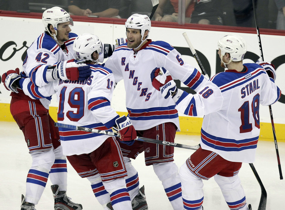 Photo -   New York Rangers defenseman Dan Girardi, second from right, celebrates with teammates Artem Anisimov, left, Brad Richards, and Marc Staal, right, after scoring against the New Jersey devils during the third period of Game 3 of an NHL hockey Stanley Cup Eastern Conference final playoff series, Saturday, May 19, 2012, in Newark, N.J. (AP Photo/Julio Cortez)
