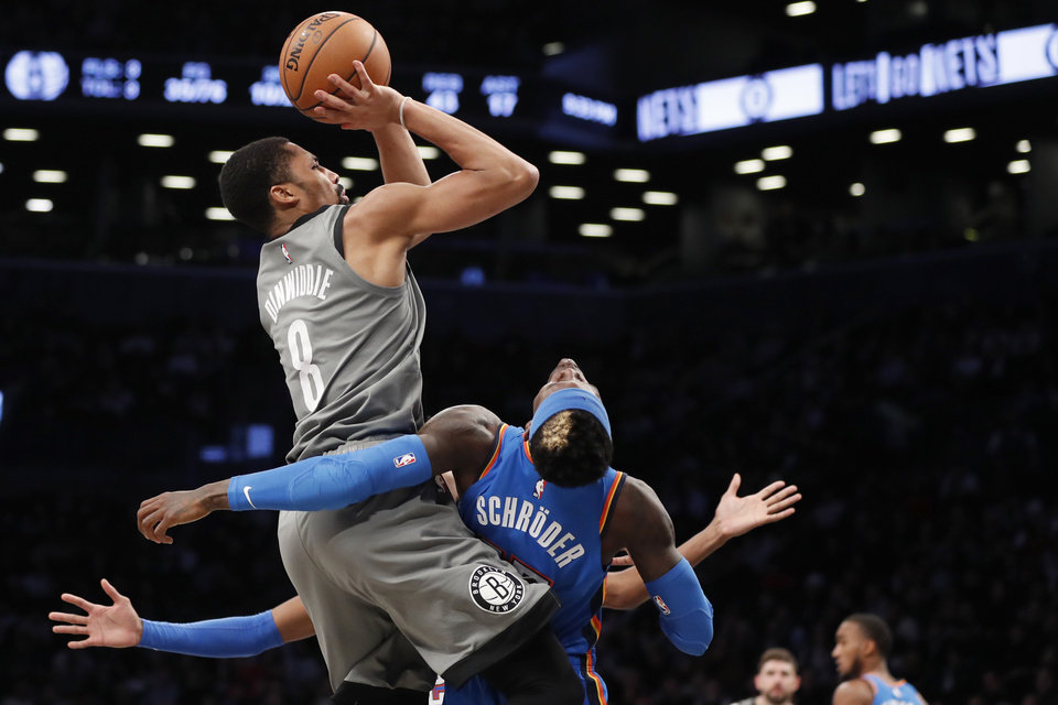 Photo - Brooklyn Nets guard Spencer Dinwiddie (8) collides with Oklahoma City Thunder guard Dennis Schroder (17) as he attempts a shot during the second half of an NBA basketball game, Tuesday, Jan. 7, 2020, in New York. The Thunder defeated the Nets 111-103 in overtime. (AP Photo/Kathy Willens)