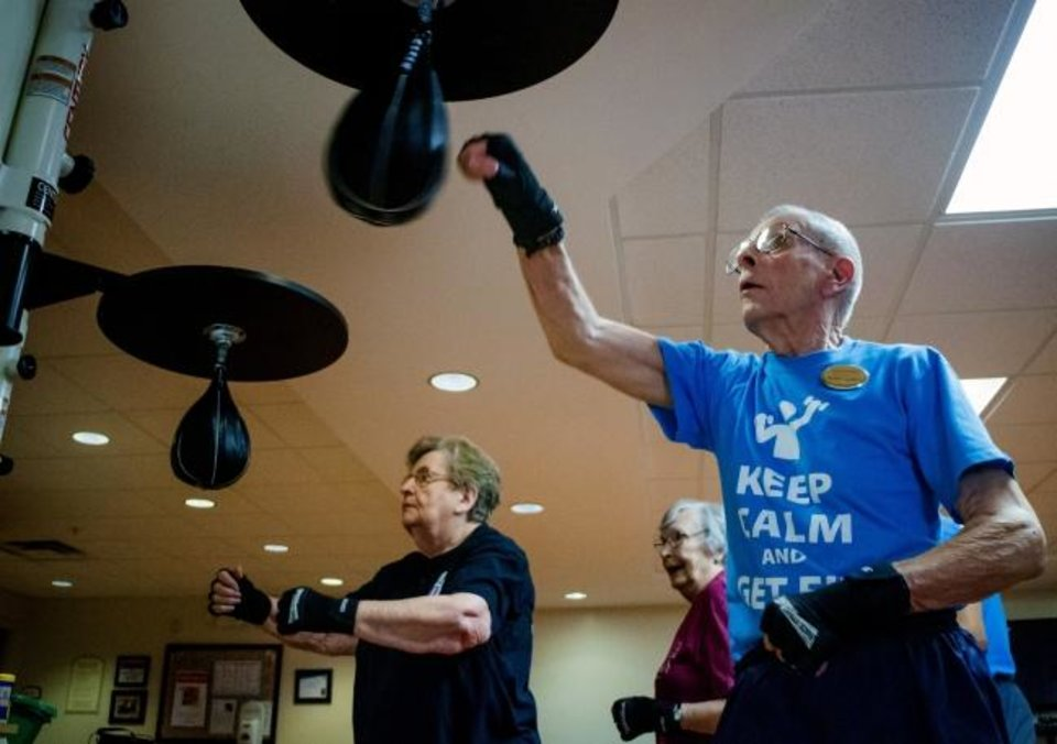 Photo -  Betty Fisher and Robert Quatro use the speed bags as they work out during a senior boxing class.  [Chris Landsberger/The Oklahoman]