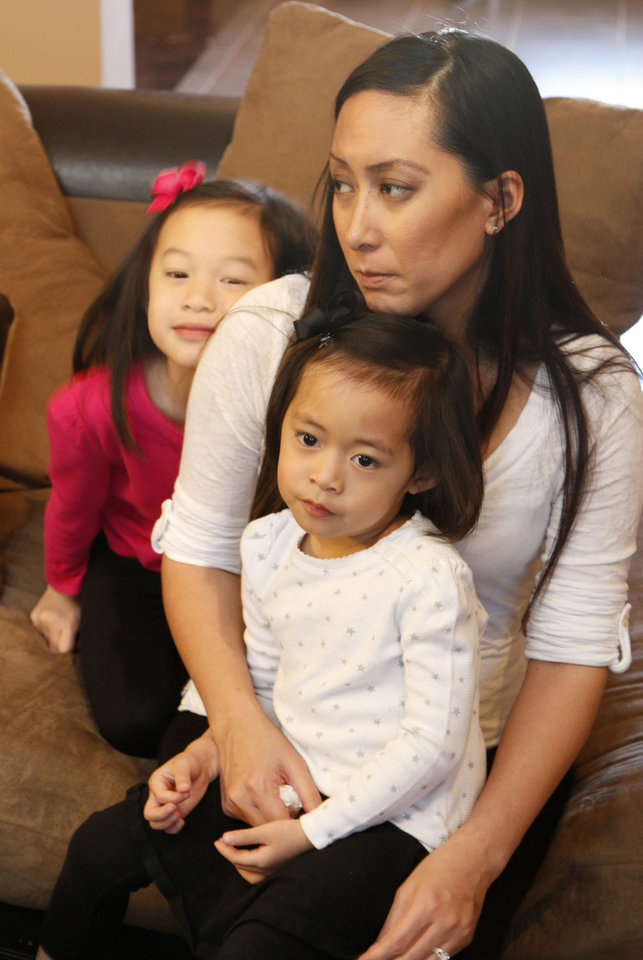 Photo - Jennifer Doan sits with her two daughters, Kylie Nguyen, 3, and Kairi Nguyen, 6, at their home in Edmond on Thursday. Doan's 2-week-old son is named after Nicolas McCabe, one of her students who died after a wall collapsed during the May 20 tornado at Plaza Towers Elementary School in Moore.  PAUL HELLSTERN - The Oklahoman