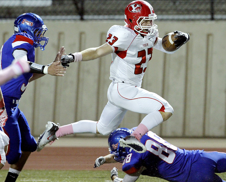 Yukon's Derek Deeds gets past Moore's Tate Alvarez (left) and Jordan Martin (bottom) to score the Millers' first touchdown in the first quarter of their high school football game at Moore Stadium in Moore, Oklahoma on Thursday, Oct. 20, 2011. Photo by John Clanton, The Oklahoman