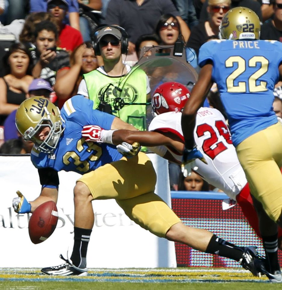 UCLA punt returner Steven Manfro, left, loses the ball in the end zone as Utah defensive back Reggie Topps, second from left, knocks Manfro away to allow Utah's Ryan Lacy, second from right, to recover the ball for a touchdown during the first half of their NCAA college football game, Saturday, Oct. 13, 2012, in Pasadena, Calif. (AP Photo/Alex Gallardo)