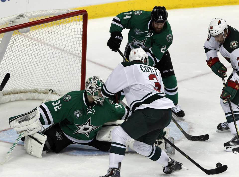 Dallas Stars goalie Kari Lehtonen (32) defends as Minnesota Wild center Charlie Coyle (3) goes to take a shot during the second period of an NHL hockey game in Dallas on Saturday, March 8, 2014.(AP Photo/ Richard W. Rodriguez)