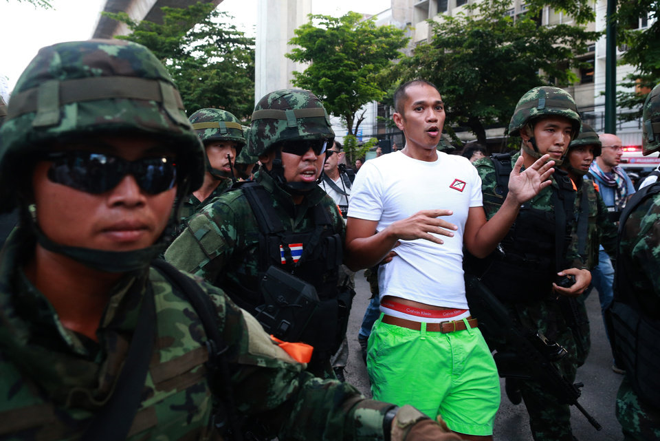 Photo - A protester is detained by Thai soldiers during an anti-coup demonstration at the Victory Monument in Bangkok, Thailand Saturday, May 24, 2014. Thailand's coup leaders said Saturday that they would keep former Prime Minister Yingluck Shinawatra, Cabinet members and anti-government protest leaders detained for up to a week to give them
