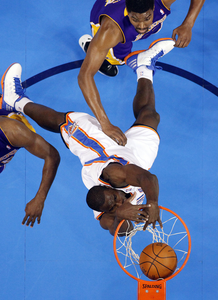 Photo - Oklahoma City's Serge Ibaka (9) dunks over Los Angeles' Andrew Bynum (17) during Game 5 in the second round of the NBA playoffs between the Oklahoma City Thunder and the L.A. Lakers at Chesapeake Energy Arena in Oklahoma City, Monday, May 21, 2012. Photo by Sarah Phipps, The Oklahoman