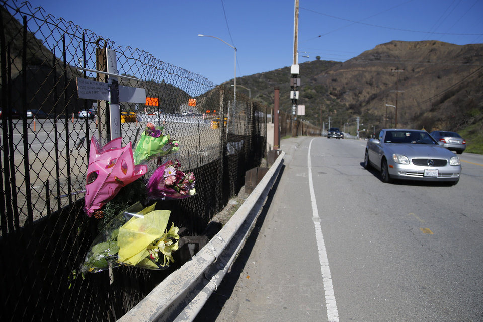 A roadside memorial for a paparazzo, who was killed by a car while darting across a street after taking pictures of Justin Bieber's Ferrari, is seen near the 405 Freeway in Los Angeles, Wednesday, Jan. 2, 2013. A paparazzo was struck and killed by a car while darting across a street after taking pictures of Justin Bieber's Ferrari when it was pulled over along a freeway in Los Angeles, police said Wednesday. (AP Photo/Jae C. Hong)