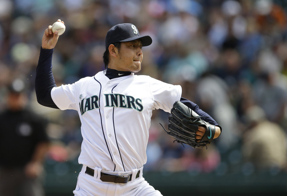 Photo - Seattle Mariners starting pitcher Hisashi Iwakuma throws against the Washington Nationals in the first inning of a baseball game, Sunday, Aug. 31, 2014, in Seattle. (AP Photo/Ted S. Warren)